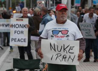 MIAMI, FL - JANUARY 09: Bob Kunst holds a sign that reads, 'Nuke Iran,' as he counter protests during an Anti-Iran War Rally held at the Torch of Friendship on January 09, 2020 in Miami, Florida. The House adopted a war powers resolution Thursday with the aim of limiting President Donald Trump's military actions against Iran. (Photo by Joe Raedle/Getty Images)