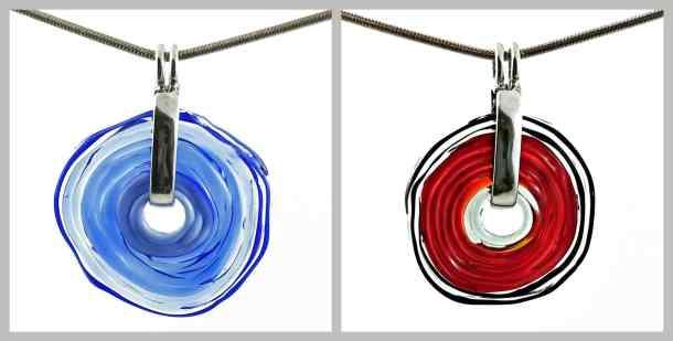 Zwei Schmuckscheiben in roter bzw. blauer Farbe. Auf eine silber-metallene Klappe montiert und mit einer Edelstahlkette versehen, werden sie gerne als Halsketten getragen.