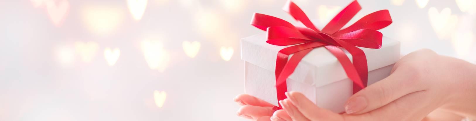 Valentinstag Geschenk mit roter Schleife in der offenen Hand vor weissem Hintergrund mit roten Herzen