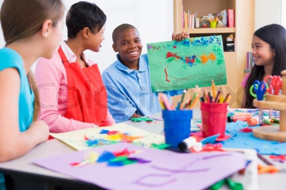 Elementary school art class with pupil discussing picture ...