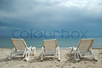 A row of three beach chairs overlooking the sea view ...