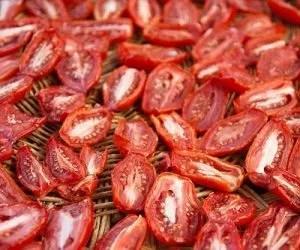 Pomodori secchi - pomodori in essicazione su cestino di vimini