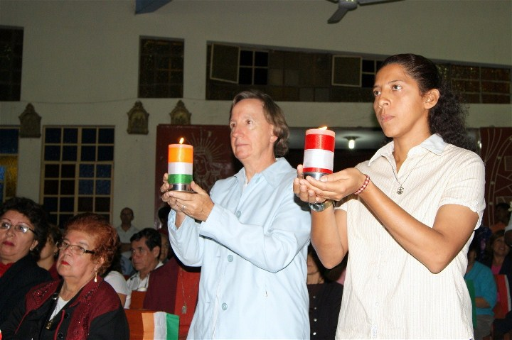 Sisters Ann Marie Smith and Patty Andonaire carry to the altar the candles decorated in the colours of Ireland and Peru