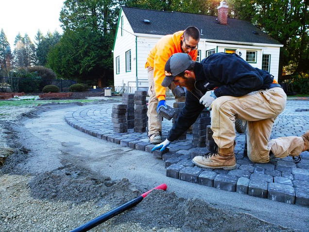 Members of the The Wall construction building a permeable outdoor meeting space