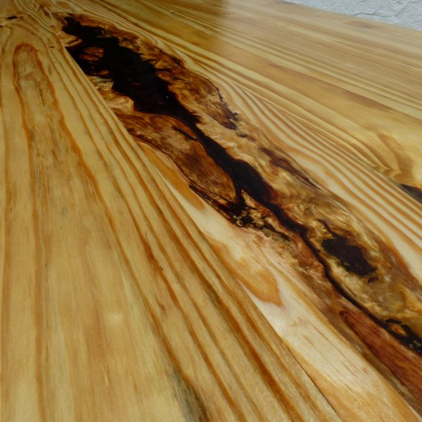 A resin filled void in a heavy reclaimed timber table top.
