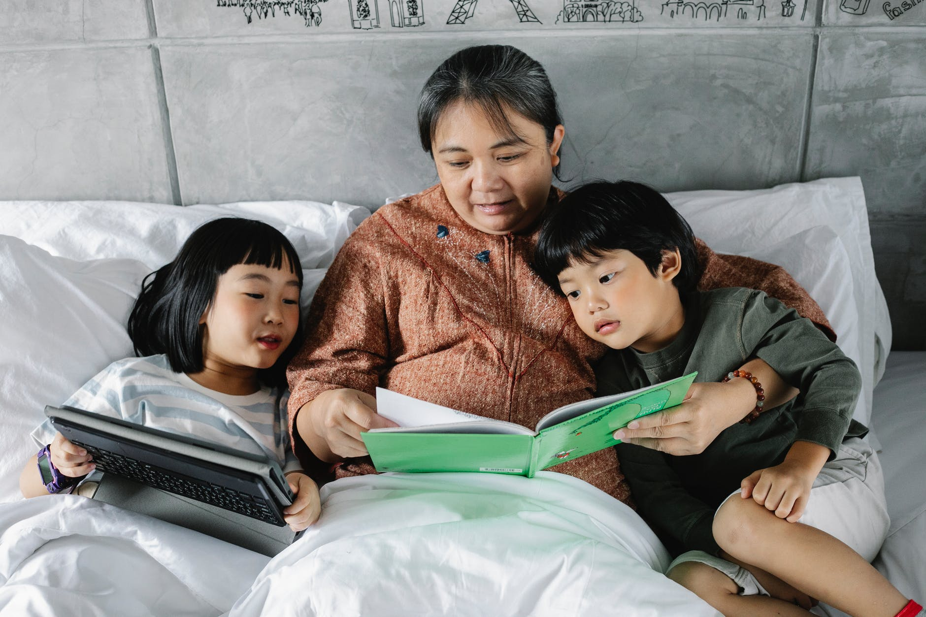 ethnic grandmother with curious children lying on bed with interesting book and tablet