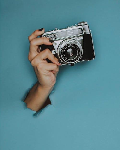 Nostalgic fandom bursts forth much like this hand holding a vintage camera