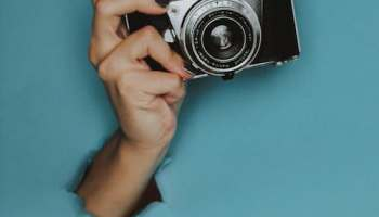 Nostalgic fandom bursts forth much like this hand holding a vintage camera