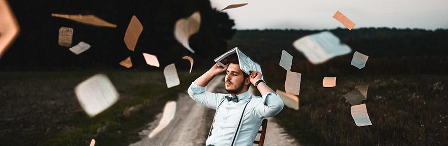 Photographie d'un homme assis sur une chaise posée au milieu d'une route et s'abritant la tête avec un livre ouvert, tenu à deux mains au dessus de sa tête. De nombreuses feuilles de papier volent tout autour de lui pour illustrer la difficulté à choisir la meilleure formation en hypnothérapie, pour devenir hypnothérapeute.