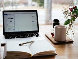 Ordinateur portable ouvert sur un bureau avec une tasse de café et un calepin pour la prise de note.