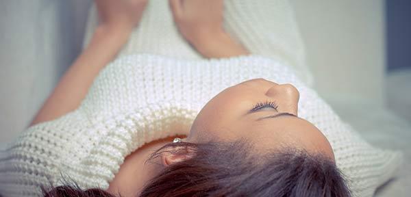 L'hypnose et l'hypnothérapie sont des solutions merveilleuses et efficaces pour traiter le stress, l'anxiété et la dépression : photographie s'une femme allongée et hypnotisée, en état de détente et de lâcher-prise.