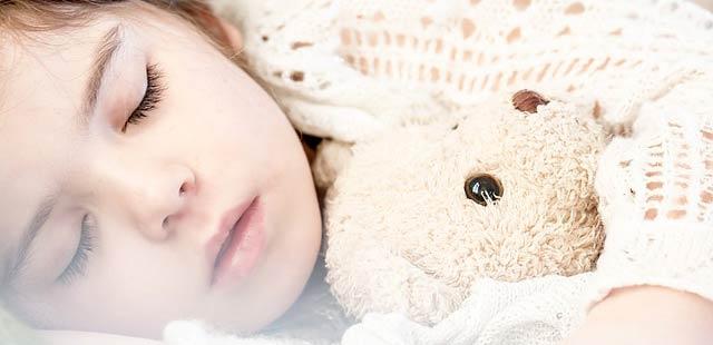 Petite fille en train de dormir mieux, allongée sur une couverture blanche avec son doudou dans les bras