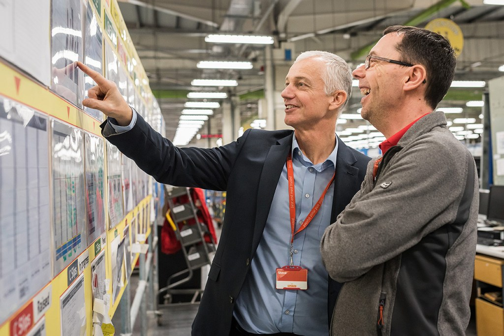 two work colleagues looking at wallchart