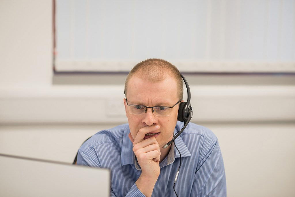 man at laptop using headset in local business setting