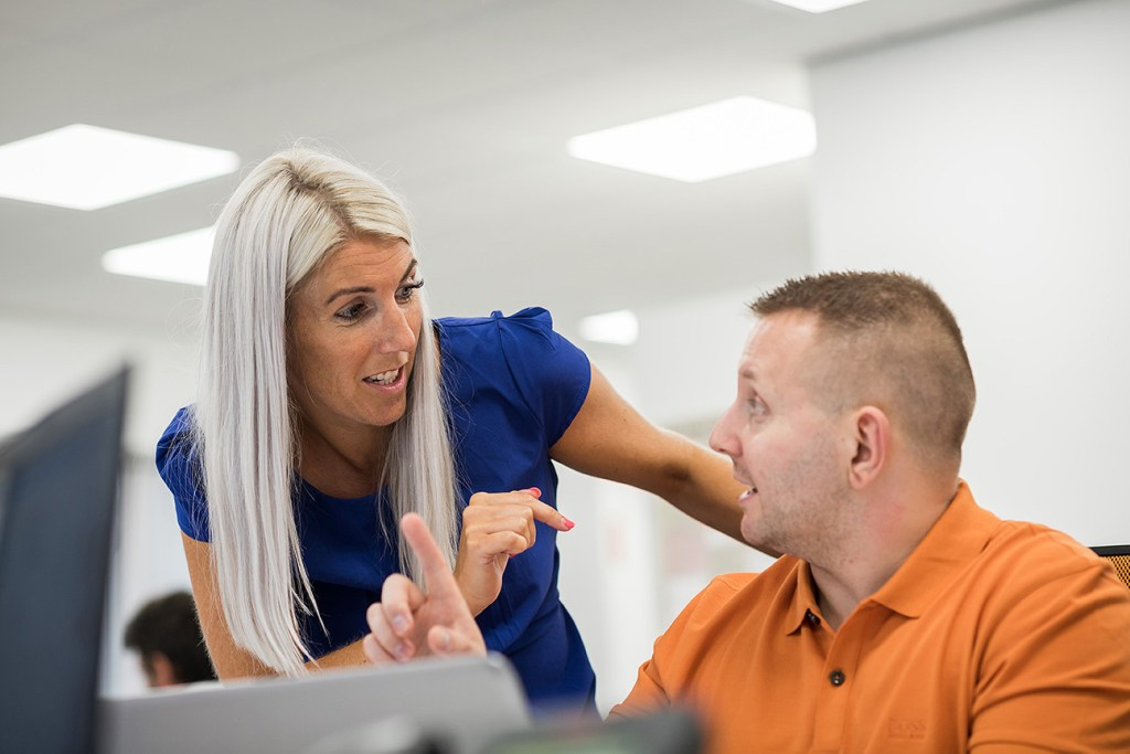 two staff members talking over computer in local business