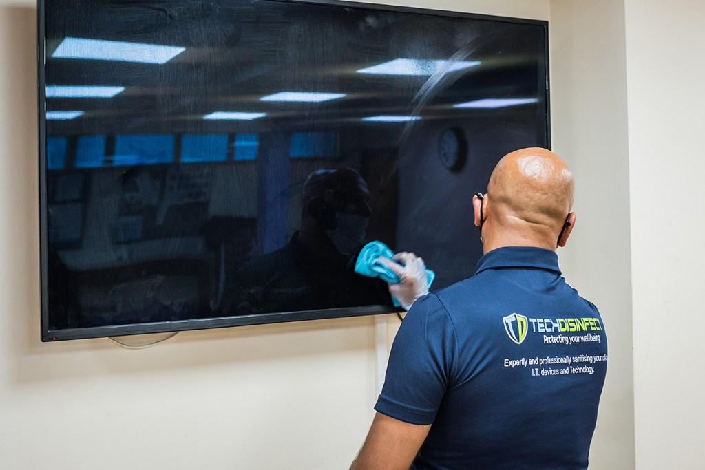 branding photoshoot photo for Tech Disinfect of man cleaning smartboard
