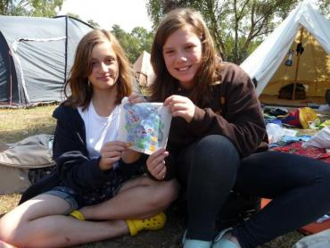 two venturers at camp showing their crafts