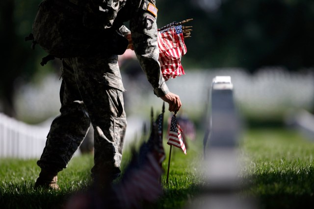 A member of the U.S. Army Old Guard places a flag at one of the over 220,000 graves of fallen U.S. military service members buried at Arlington National Cemetery, May 24, 2012. Memorial Day will be commemorated this weekend across the United States.    REUTERS/Jason Reed  (UNITED STATES - Tags: MILITARY TPX IMAGES OF THE DAY)