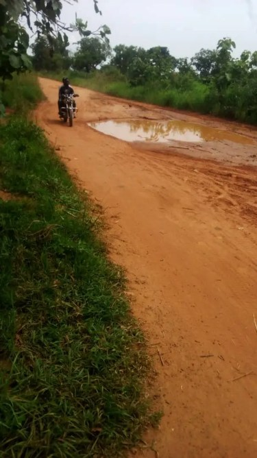 Road with water dug out and motorbike in Oti region