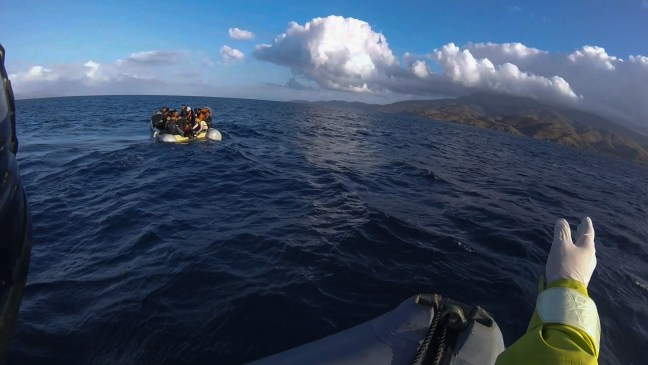 Refugee Rescue's crew on Mo Chara attempt to guide a dinghy to safe land.