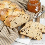Baked and golden Cinnamon Raisin Challah braid rests on a wooden trivet that is draped with a navy and brown napkin. The loaf has two slices cut and resting at the front of the loaf. A knife and apricot jam sit to the side.