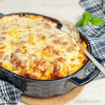 Meaty Baked Pasta is hot and cheesy from the oven in a blue casserole dish with handles. There is a serving spoon half tucked into the pasta. The dish rests on a cork pot holder that is draped with a white and navy towel. Fresh basil sits in the background.