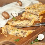 A baked Mushroom Gruyere Tart from Compelled to Cook is cut into wedges on a cutting board that is draped with a striped towel and scattered with mushrooms.