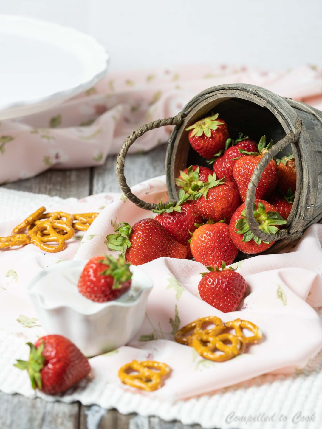 A basket of fresh strawberries tipped over and spilling out, surrounded with pretzels and a cup of yogurt.