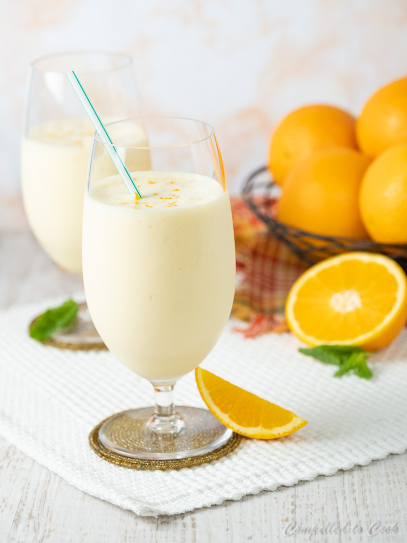 Orange Yogurt Smoothie in a tall stemmed glass garnished with orange zest and a straw.