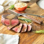 Steak with Balsamic Butter Sauce sliced and ready to serve garnished with fresh rosemary.