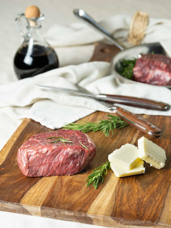 Tenderloin steak, butter and balsamic vinegar arranged on a wooden board in preparation for Steak with Balsamic Butter Sauce