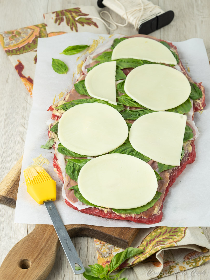 Flattened flank steak layered with prosciutto, basil and provolone in preparation for Beef Roulade.