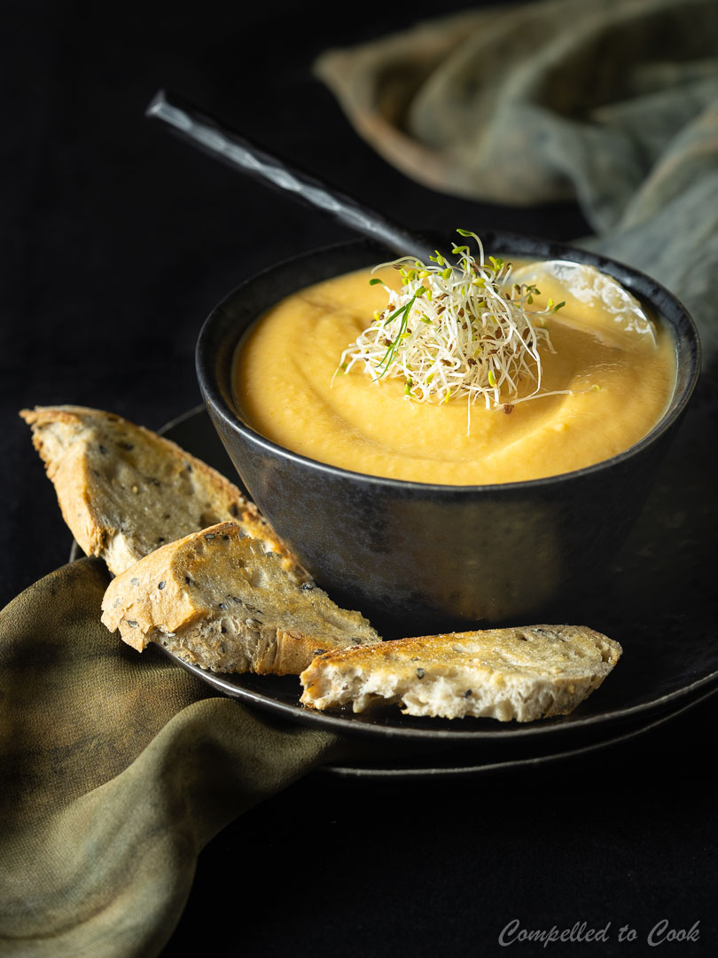 Roasted Vegetable Soup served in a black bowl with crusty bread.