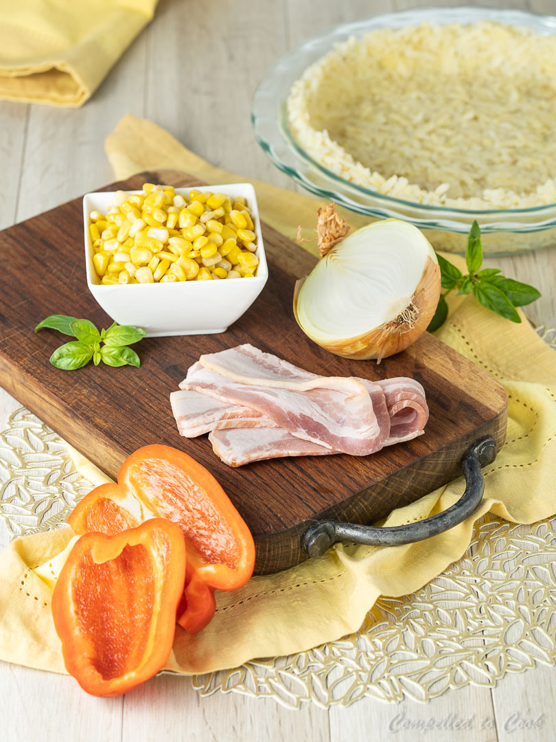Ingredients for Corn and Bacon Quiche arranged on a wooden cutting board on a yellow napkin.