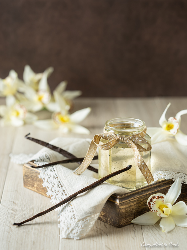 A small glass jar of Vanilla Bean Syrup resting in a wooden tray draped with a laced napkin.