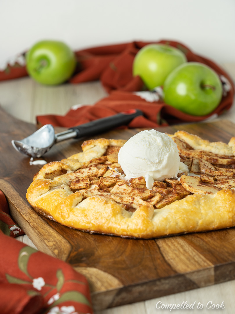 Freshly baked Apple Galette with Almond Pastry sitting on a wooden board with a scoop of vanilla ice cream in the centre.