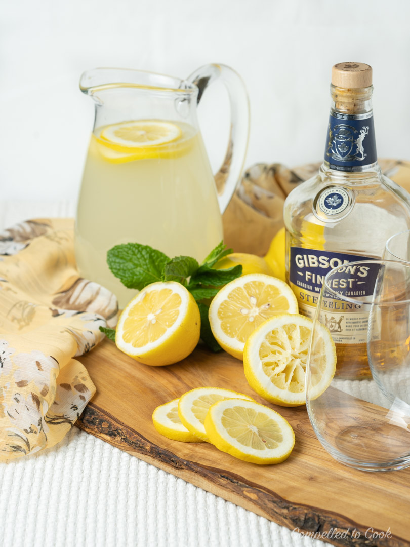 Ingredients for Whiskey Lemonade displayed on a rustic wooden board.