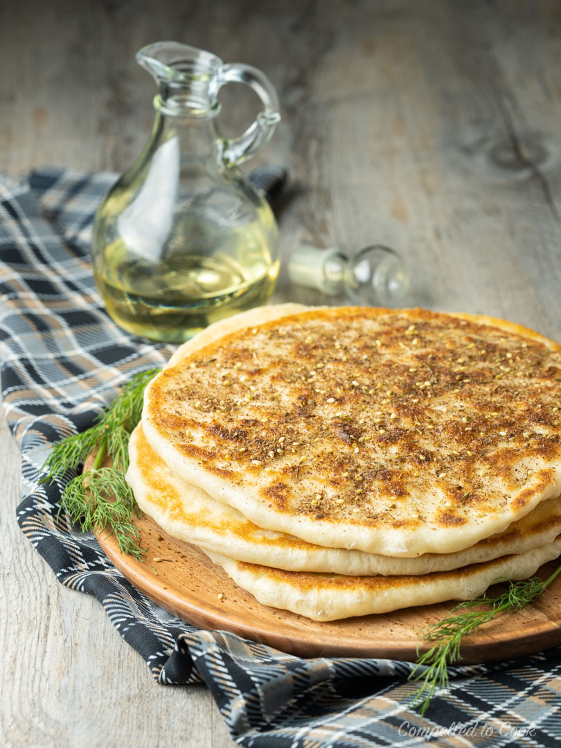 Skillet Flatbread stacked three high on a wooden serving plate and garnished with zahtar.