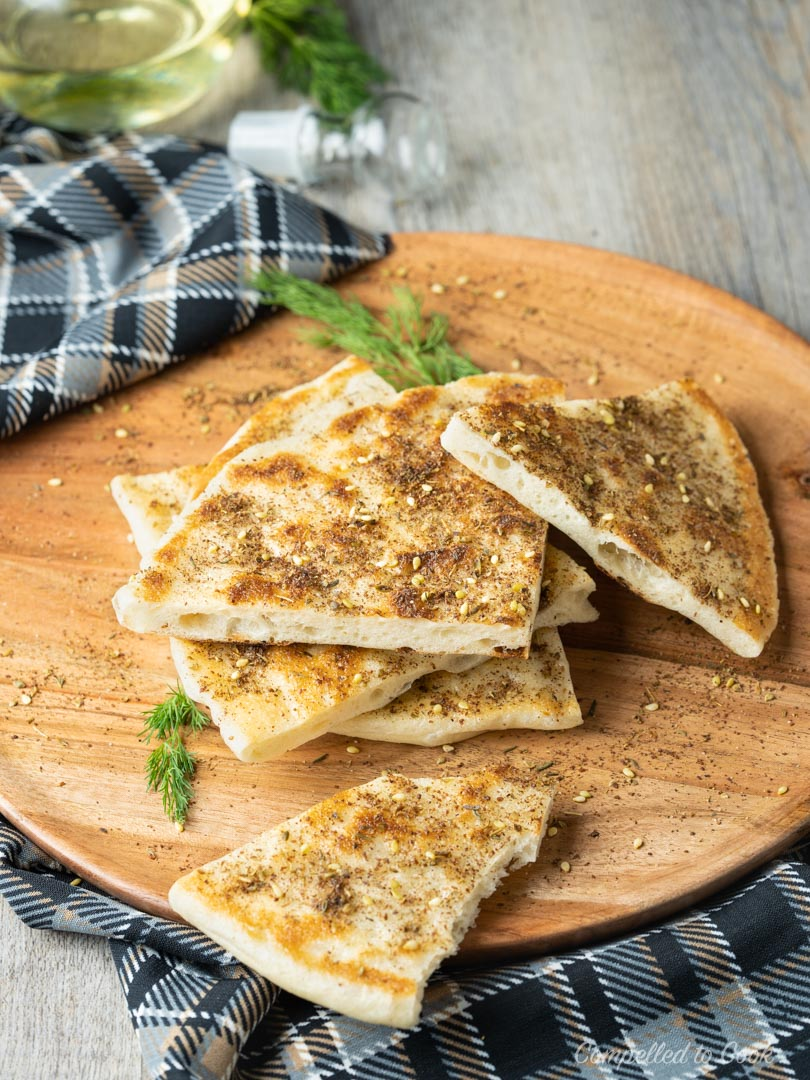 Skillet Flatbread cut into triangles and served on a wooden serving plate and garnished with zahtar.