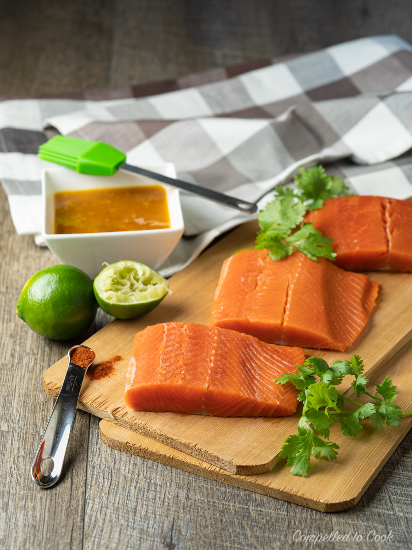 Fresh salmon fillets on a cedar plank ready for the grill and Mango Chipotle Glazed Salmon.