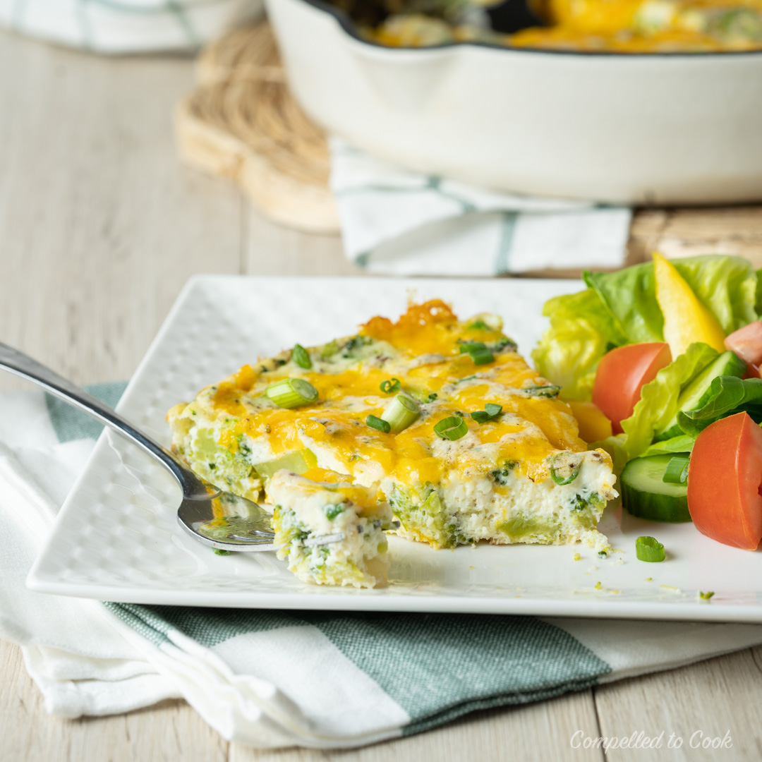 A slice of Broccoli Chedddar Frittata served with a garden salad on a white plate and resting on a green and white checkered kitchen towel.