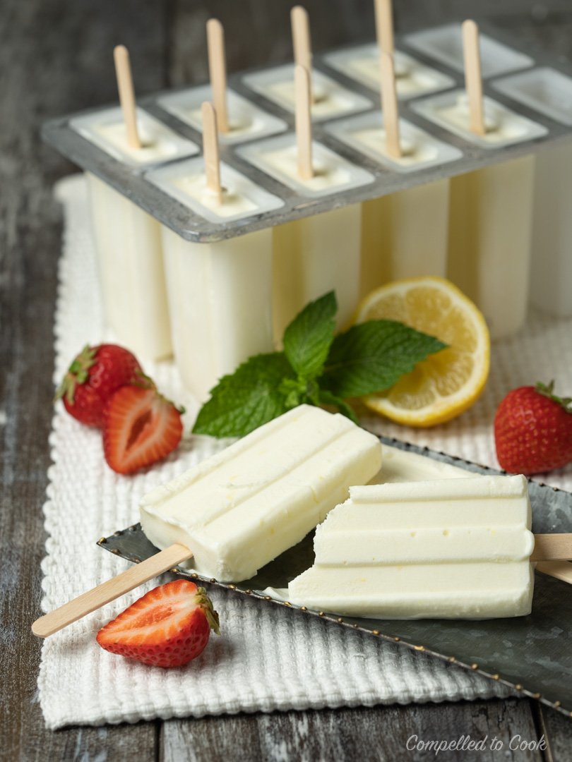 Creamy Lemon Pops in a popsicle mold with a tray of Creamy Lemon Pops garnished with strawberries and mint in the foreground.