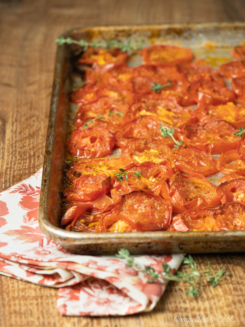 A sheet pan of roasted tomatoes in preparation for Tomato and Roasted Garlic Pie.