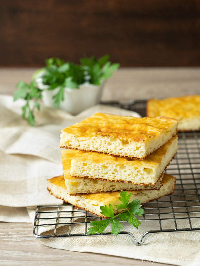 A stack of Low Carb Almond Bread resting on a wire rack with a fresh parsley garnish.