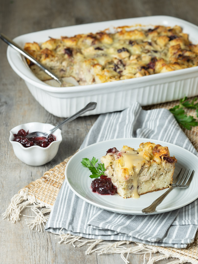 A piece of baked Leftover Turkey Dinner Strata served with gravy and cranberry sauce.