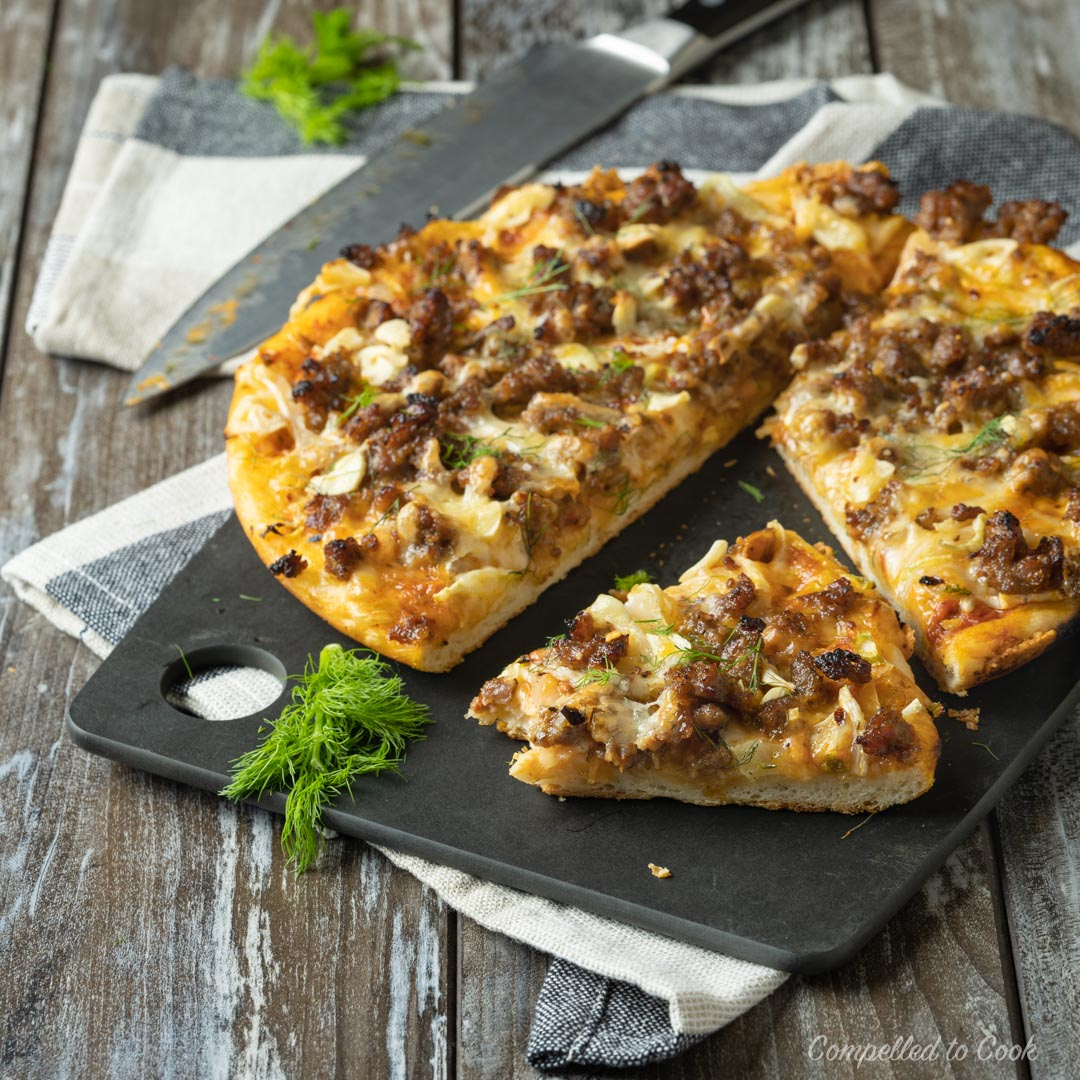 Sausage and Fennel Cast Iron Pizza garnished with fennel fronds and cut into slices on a black cutting board.