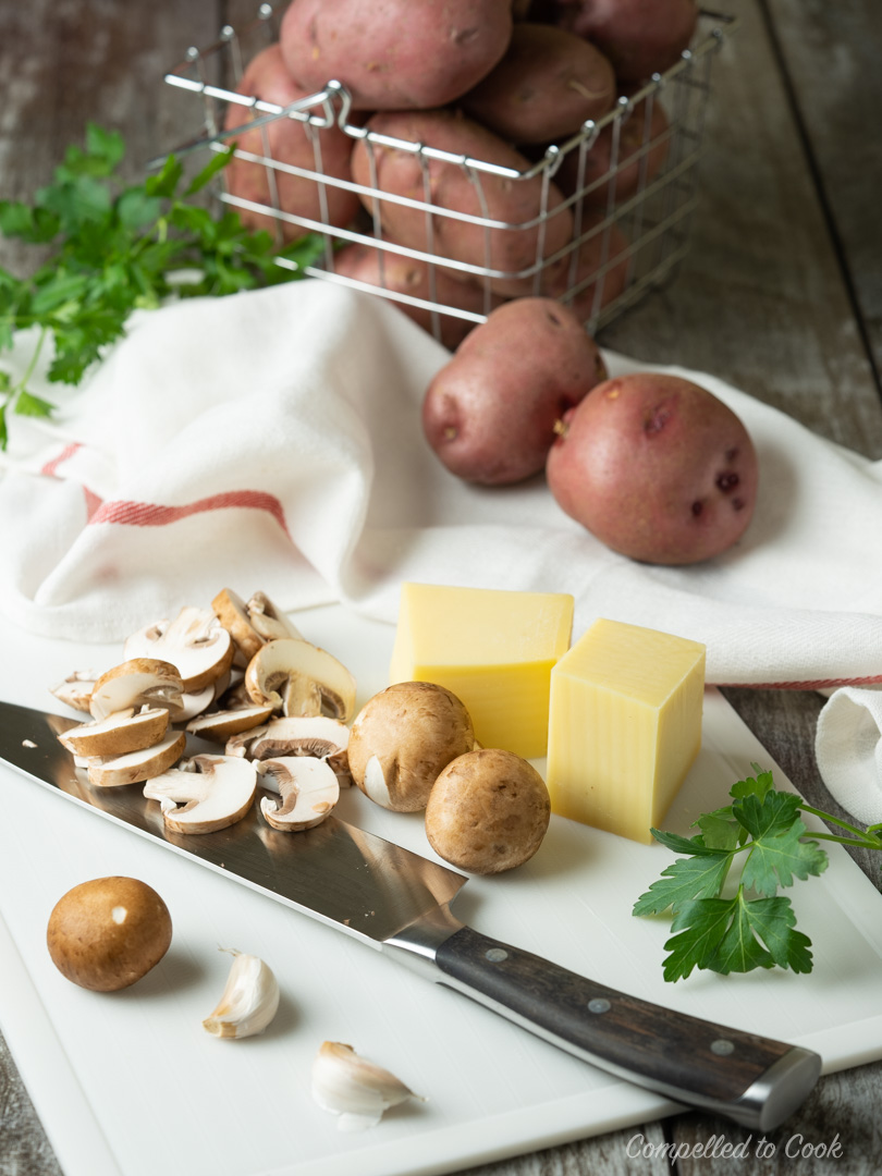 Sliced mushrooms, gruyere cheese and potatoes in a basket are being prepped for Potato and Mushroom Gratin.
