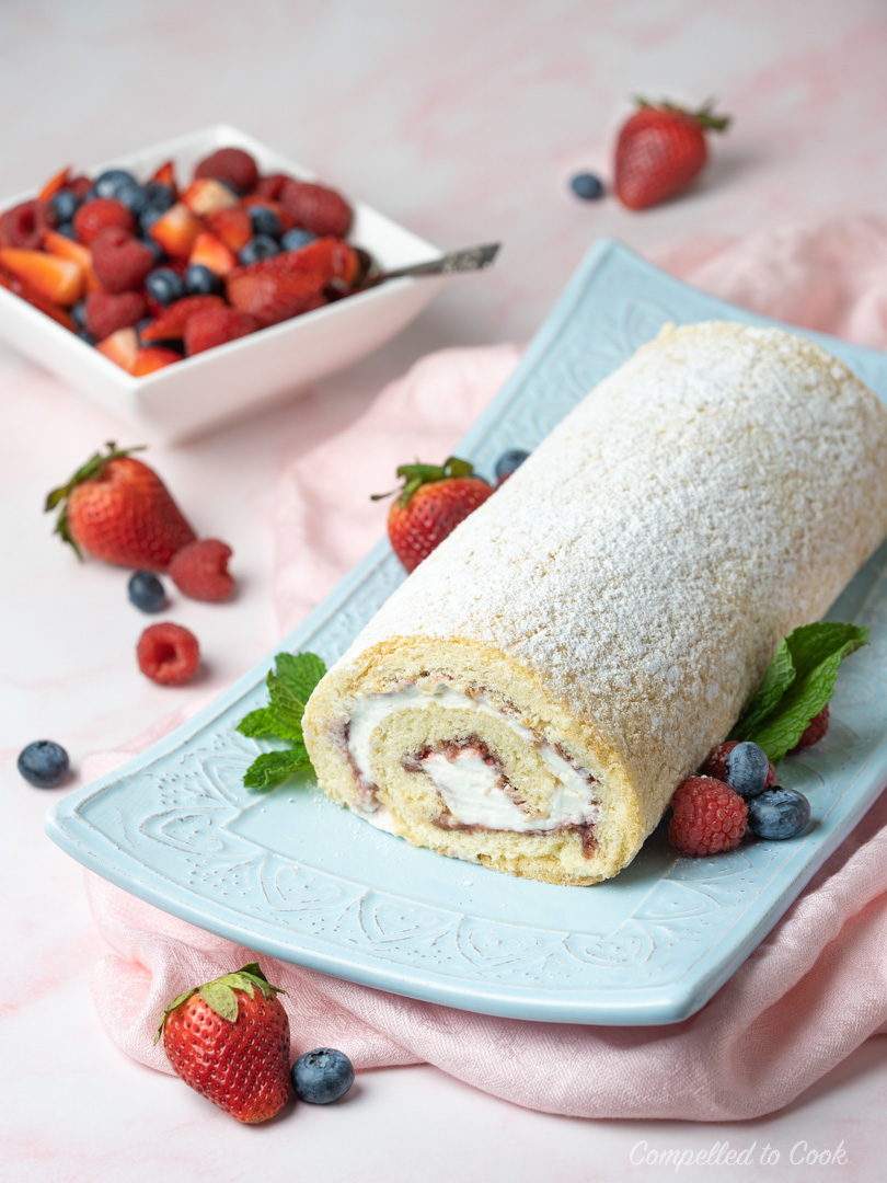 Raspberry Cream Roll served on a light blue platter garnished with fresh berries.