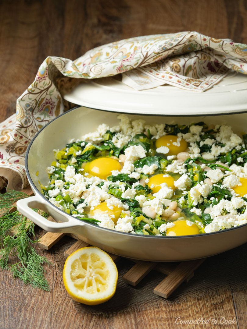 Spinach and Feta Shakshuka in a shallow braiser ready to cook the eggs.