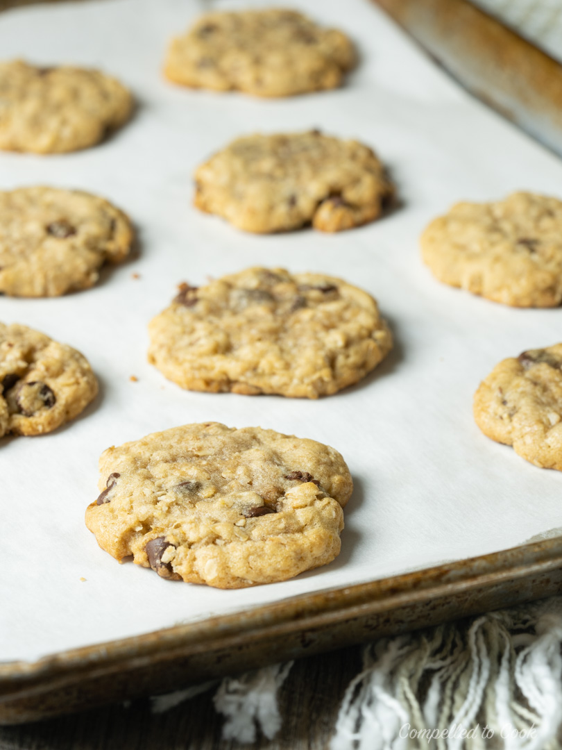 Baked Chocolate Chip Oatmeal Cookies on a parchment lined baking tray.